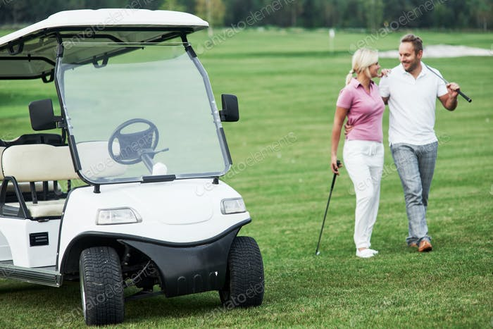 The golf cart with lovely couple walking near the vehicle and smiling