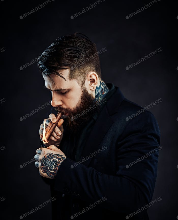 Elegantly dressed bearded male with tattoos on his neck and hand lights a cigar