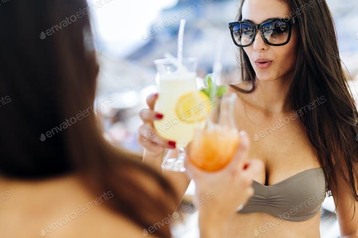 Beautiful women on beach enjoying cocktails