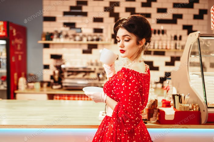 Glamour pin up girl drinks coffee in retro cafe