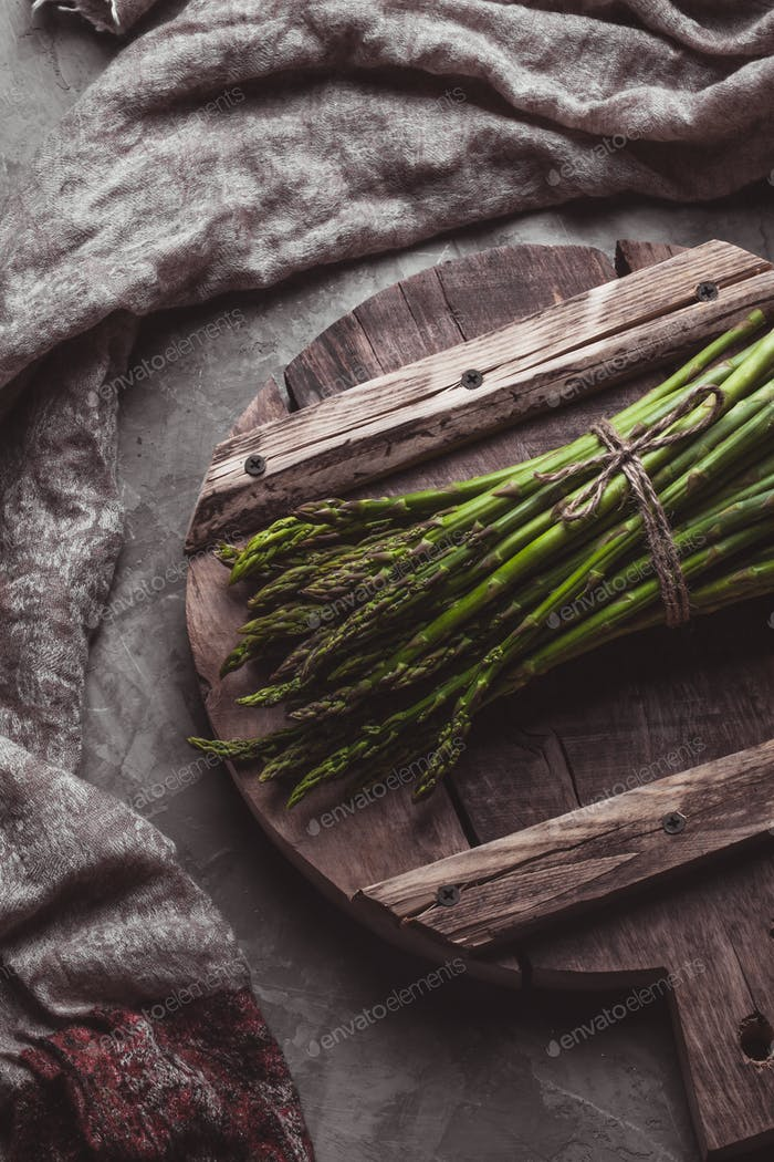 Asparagus on a cutting board. Healthy food, health on a concrete background. Wholesome healthy food