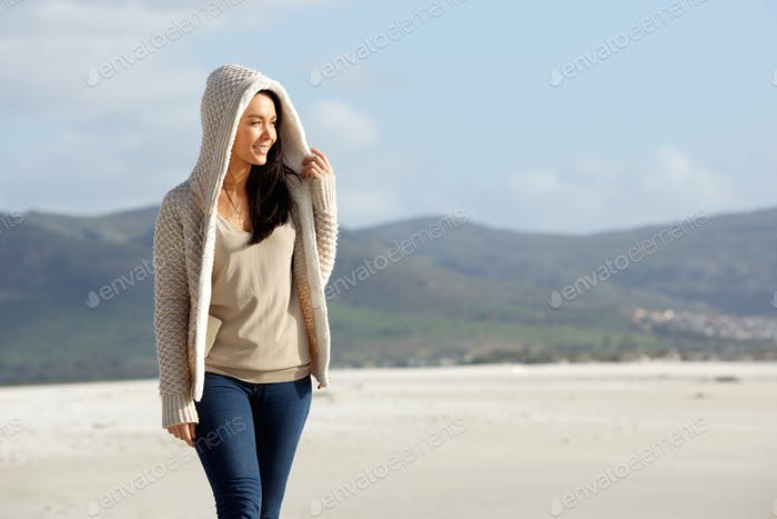 Young woman wearing a sweater walking at the beach