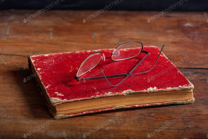 Old book and eye glasses on wooden desk