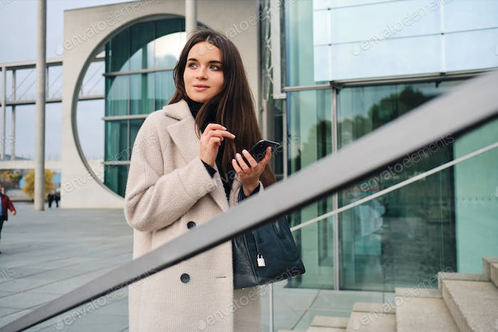 Thumbnail for Young pretty businesswoman in coat with handbag dreamily using cellphone