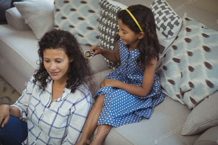 Cute daughter combing mothers hair in living room