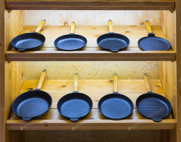 Frying pans on wooden shelf, cooking tools