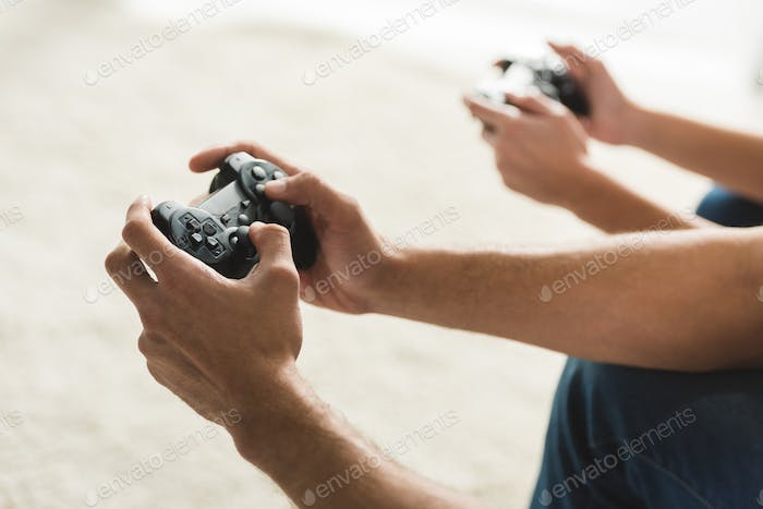 cropped shot of couple playing computer games with gamepads