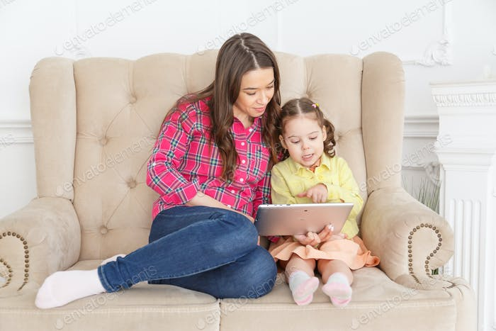Young mother teaches a child with a tablet