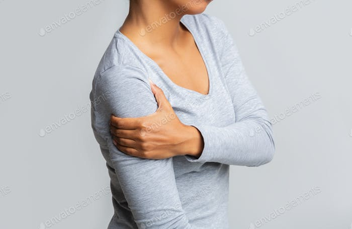 Afro woman holding her forearm over grey background