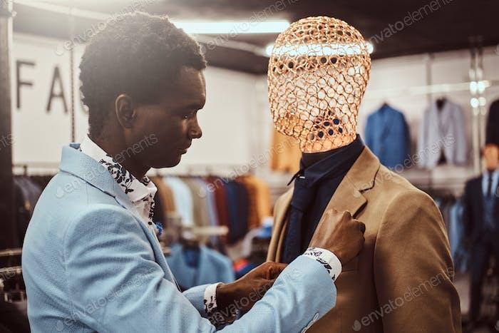 Элегантно одетый афро-американский мужчина работает в магазине классической мужской одежды.