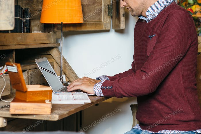 Crop young man using laptop at home