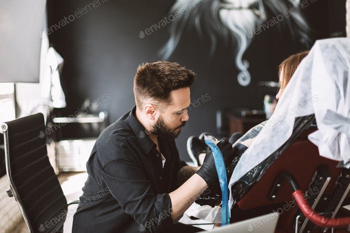 Professional tattoo master dreamily doing tattoo on girl hand us