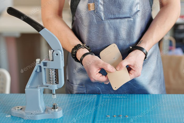 Hands of creative leatherworker putting tiny metallic knobs into beige leather