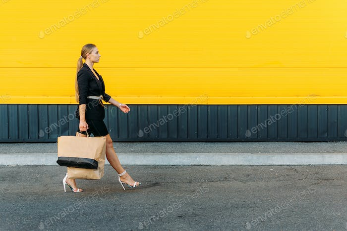 Shopping, sale concept. Stylish fashionable young woman walking and holding shopping bags on yellow