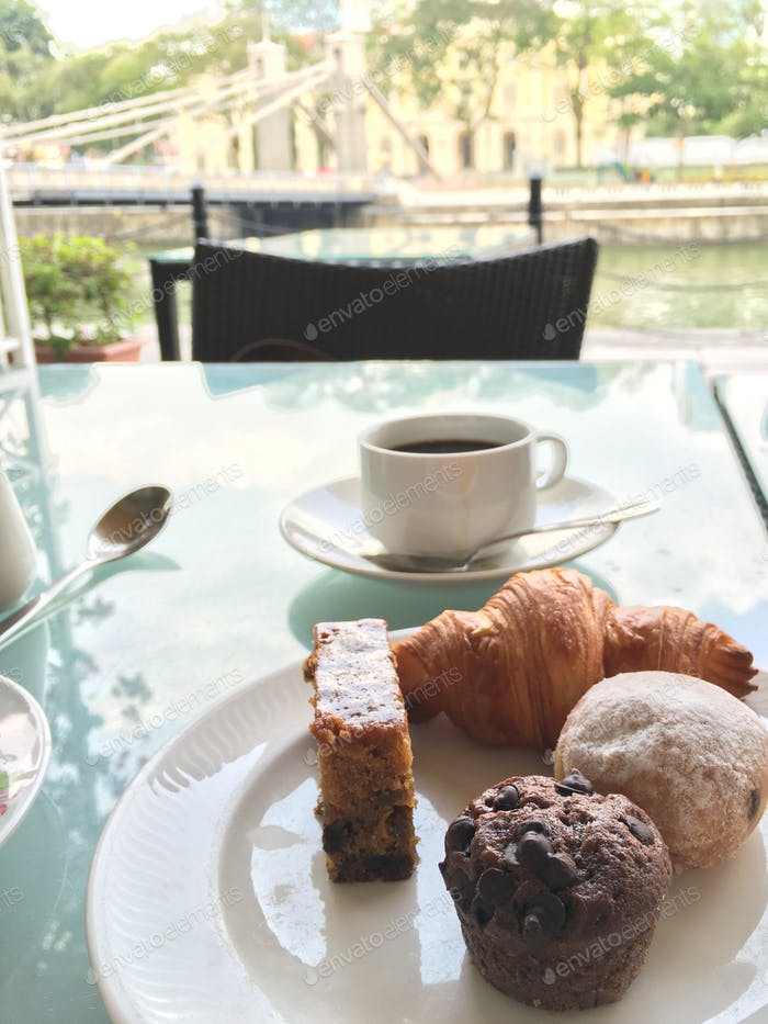 Morning cup of coffee with selection of sweet cakes.
