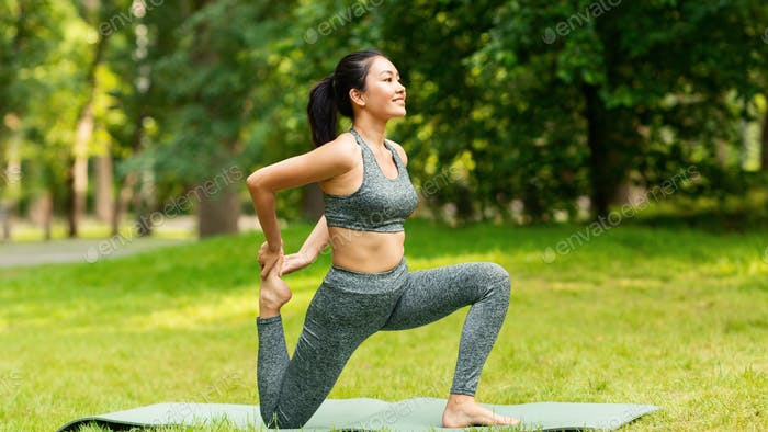 Sporty Asian girl doing yoga stretching exercises on mat at summer park