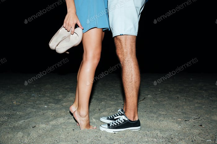 Legs of young couple standing on the beach at night