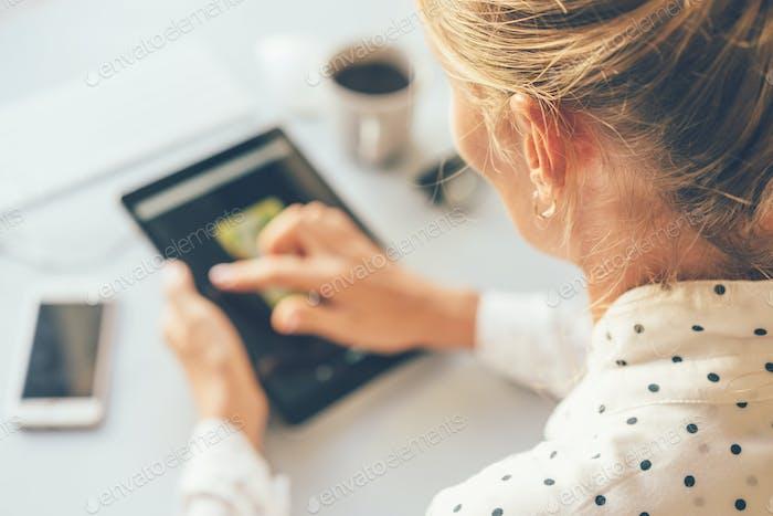 Eine Bloggerin sucht mit einem Touchscreen nach Informationen im Internet.