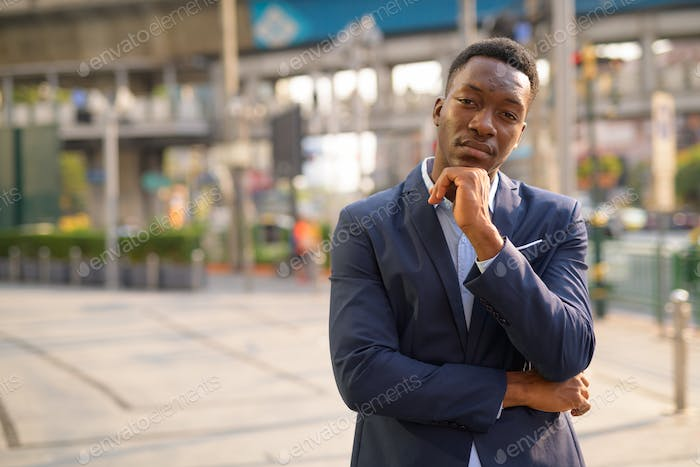 Young handsome African businessman thinking in the city