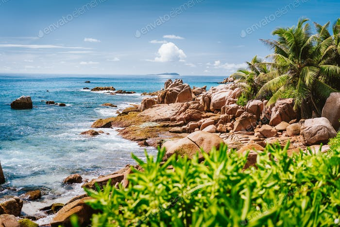 Granite rocky coastline on tropical La Digue island, Seychelles. Beautiful palm trees, boulders and