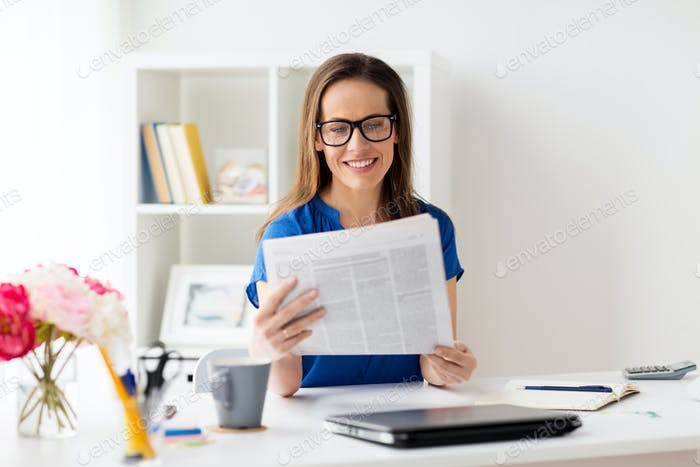 happy woman in glasses reading newspaper at office