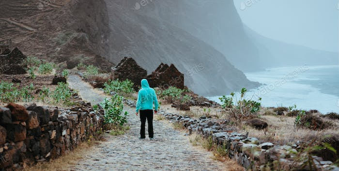 Male hiker admiring beautiful dramatic landscape of rugged coastline on the trekking trail to