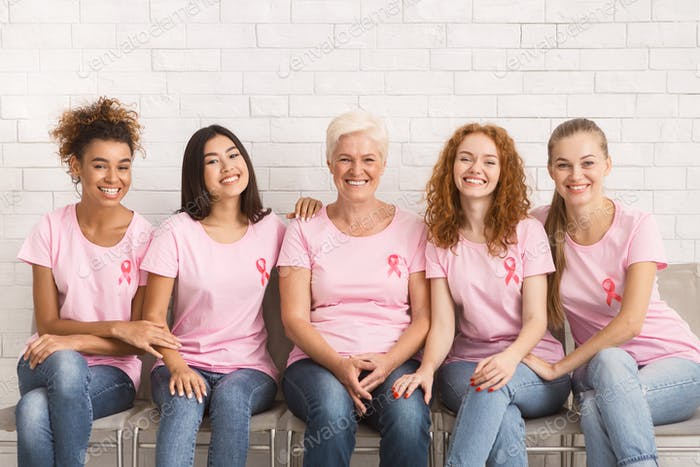 Positive Women In Breast Cancer T-Shirts Sitting On Couch Indoor