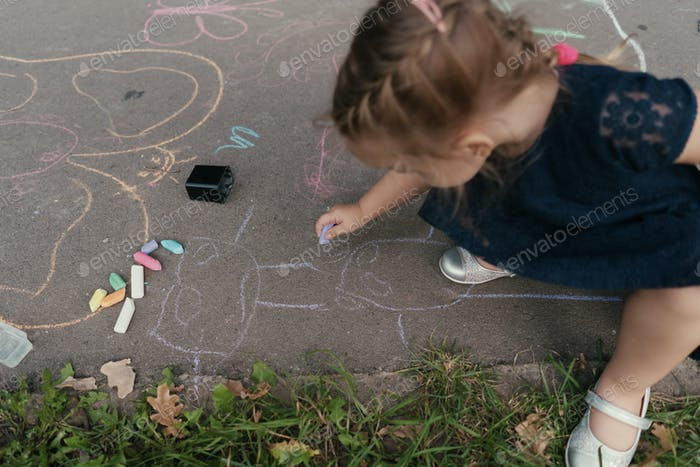 Cute girl draws on the asphalt with chalk