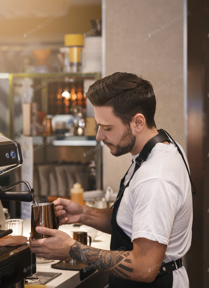 Professional Barista Making Coffee Using Coffee-Machine Standing In Cafe