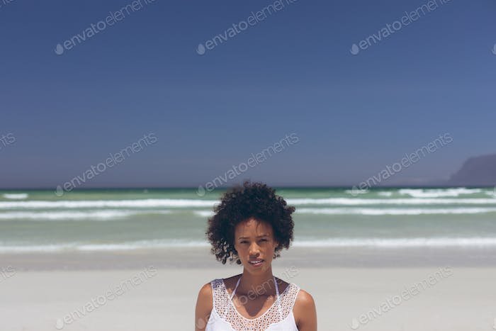 Portrait of beautiful young mixed-race woman looking at camera standing at beach on a sunny day