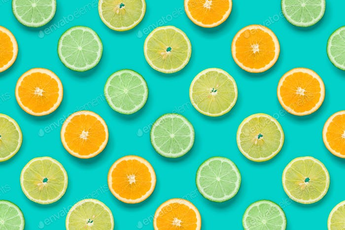 Citrus Fruit pattern on blue background. Orange, Lime, Lemon slices background. Flat lay, top view.