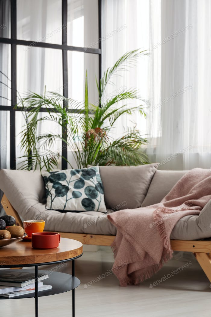 Comfortable beige scandinavian settee with patterned pillow in bright living room interior