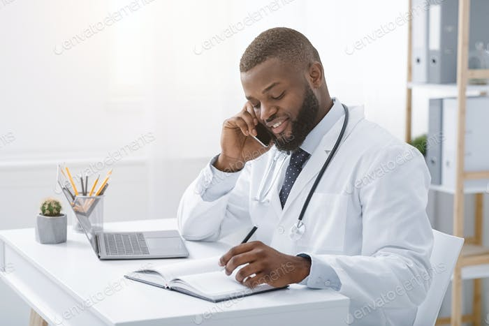 Young african doctor talking to patient on phone