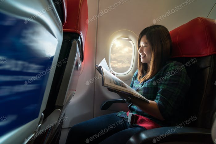 Asia young woman reading the magazine while traveling inside the airplane