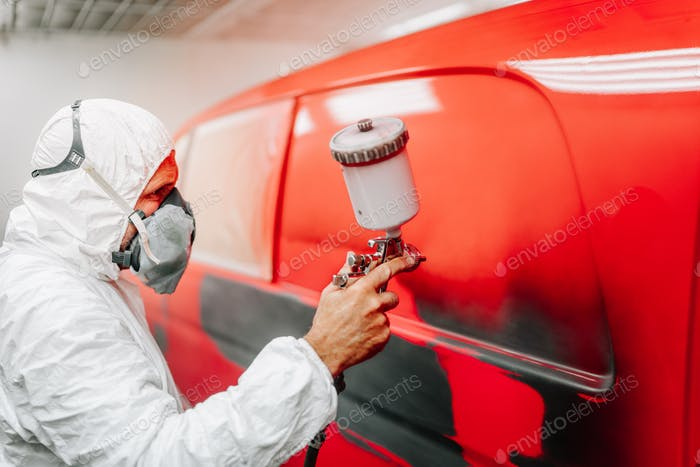 worker painting a car in a special painting box, wearing a white costume and a breathing helmet