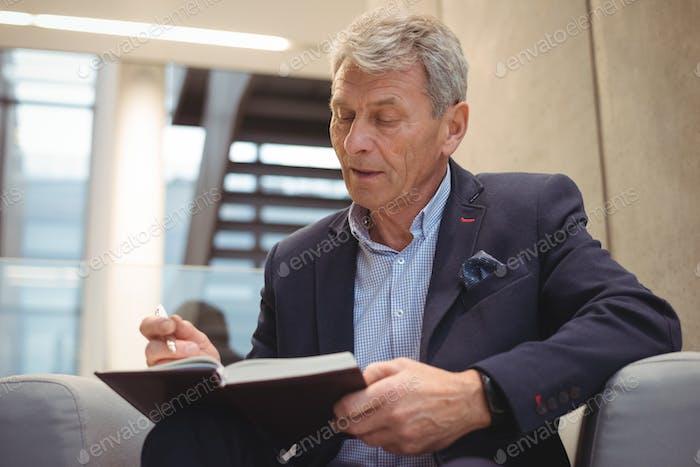 Attentive businessman writing in organizer