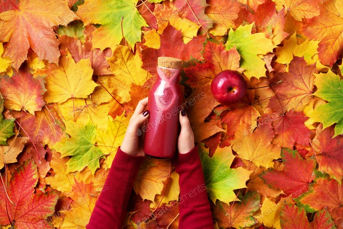 Female hands holding bottle of red drink - smoothie or juice from vegetables, fruits and berries