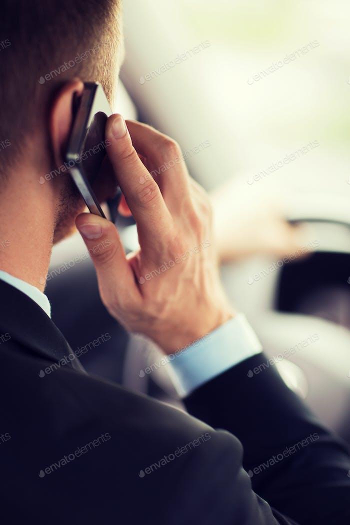 Mann mit dem Telefon während des Autofahrens