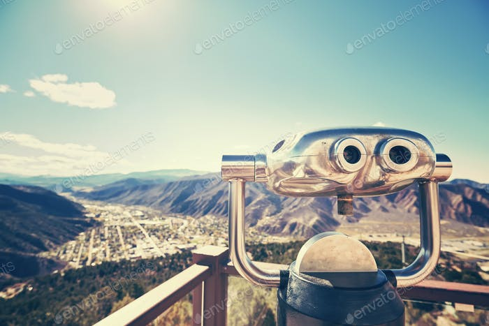 Color toned photo of binoculars looking out over a valley.