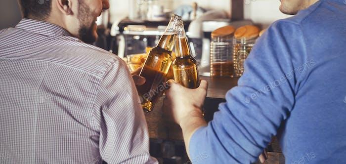 Mates Clinking Bouteilles De Bière Dans Pub