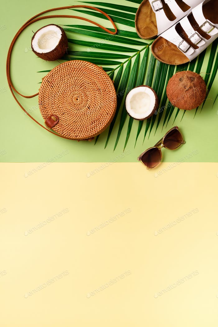 Round rattan bag, coconut, birkenstocks, palm branches, sunglasses on green background. Banner. Top