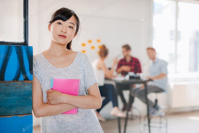 Young asian business woman standing in office