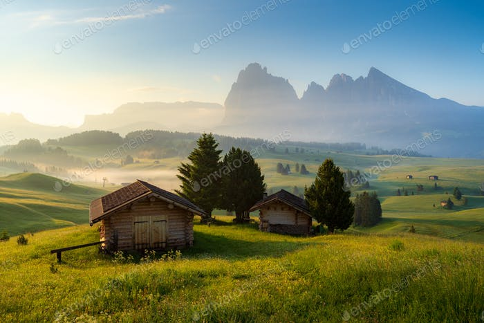 Chalets at Seiser Alm with Langkofel mountain in background at sunrise, Dolomites, Italy