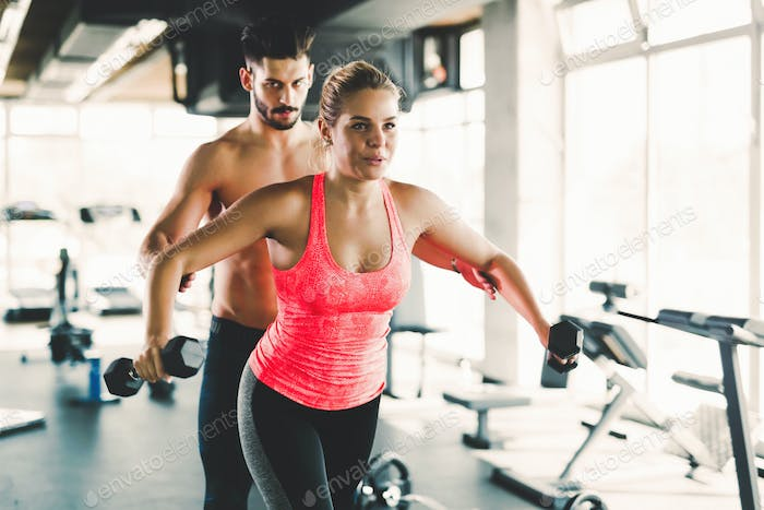 Personal trainer helping young woman with exercises for shoulders
