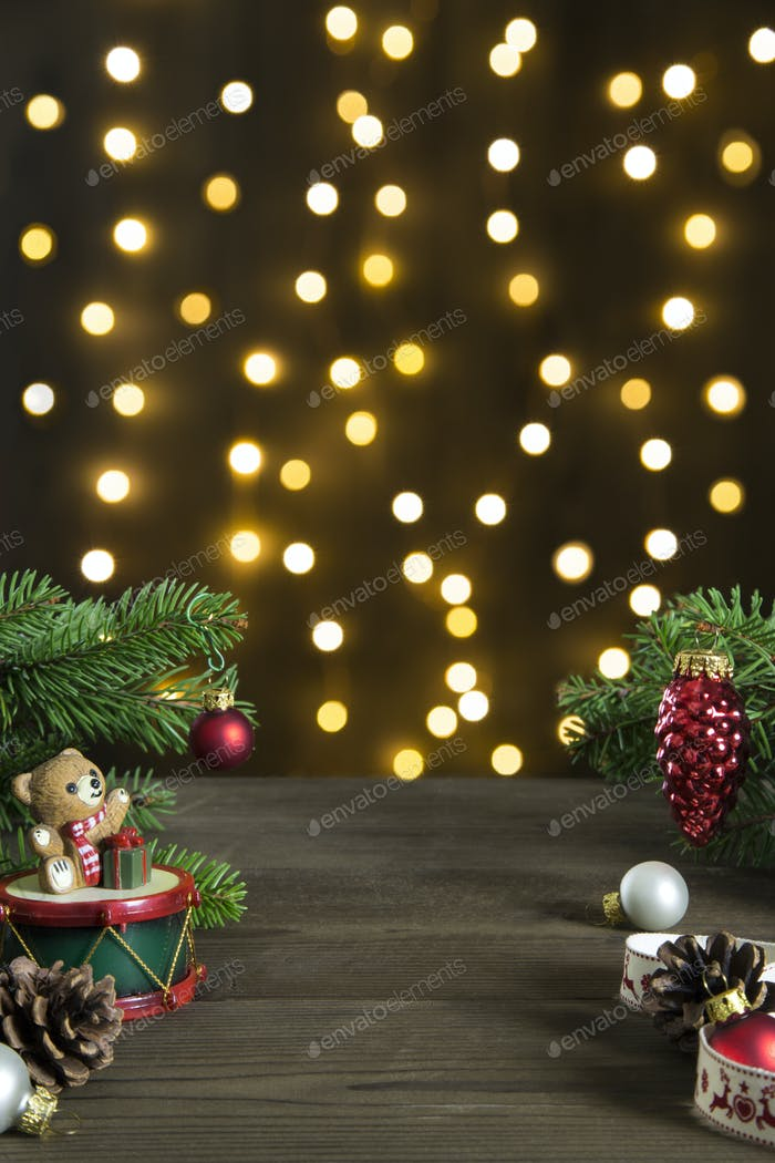 Christmas composition with cute teddy bear glass balls and fir on a wooden top with bokeh of lights