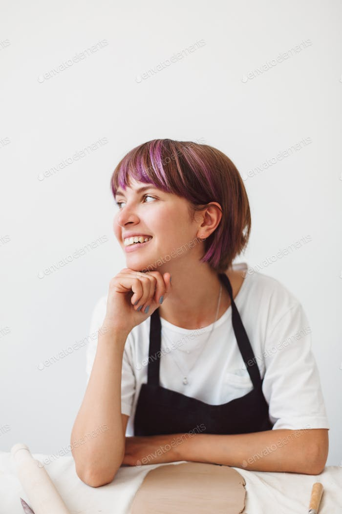 Beautiful smiling girl with colorful hair in white T-shirt dreamily looking aside