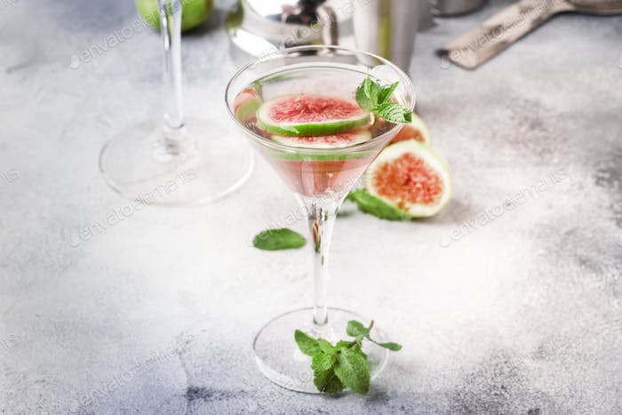 Pink fig martini cocktail in shot glass on gray table