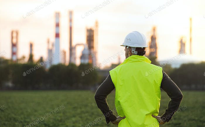 Rear view of young engineer standing outdoors by oil refinery, arms on hips