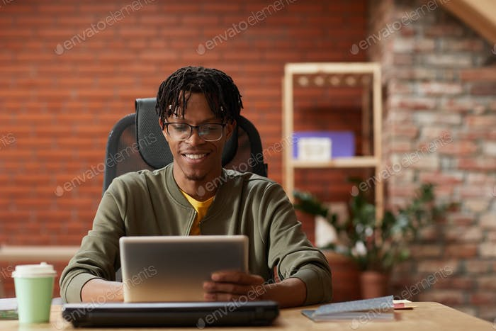 African businessman working on tablet pc