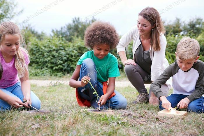 Weibliche Teamleiter zeigt Gruppe von Kindern auf Outdoor-Camping-Trip Wie man Feuer macht